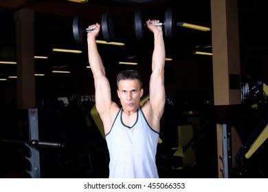 Happy handsome man athlete training at gym hall