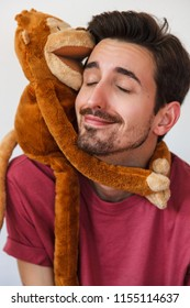 Happy and handsome Man with beard playing with stuffed animal. Monkey stuffed. Kid Stuff