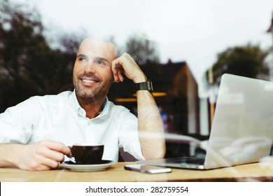 Happy handsome man at cafe drinking coffee and looking out the window