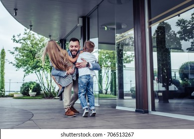 Happy handsome man with children on hands. Dad is arriving home from work. Little charming daughter and son are meeting him. Family is having fun in park.