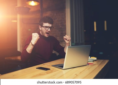 Happy handsome man dressed in casual clothing emotionally celebrating victory of favorite team while watching live streaming video and making sport betting on laptop computer