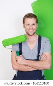 Happy handsome man in dungarees painting his house standing smiling at the camera with his paint roller his folded arms in front of a half finished green wall