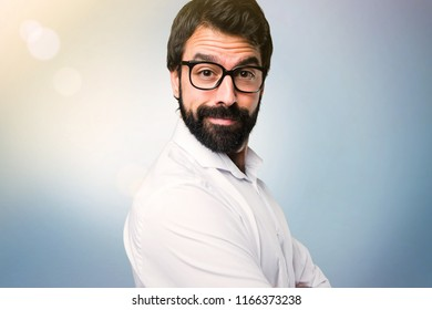 Happy handsome man with glasses on blue background