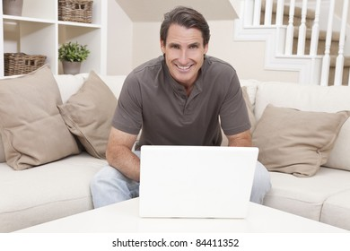 Happy handsome man in his thirties sitting at home on a sofa using a laptop computer