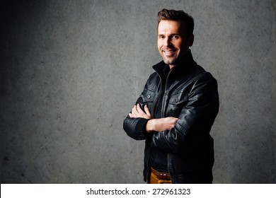 Happy handsome man in leather jacket standing against concrete wall