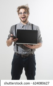 Happy handsome man or male student, businessman, with beard and stylish, blond hair, in nerd glasses talking on smartphone with laptop computer. Communication and using technology