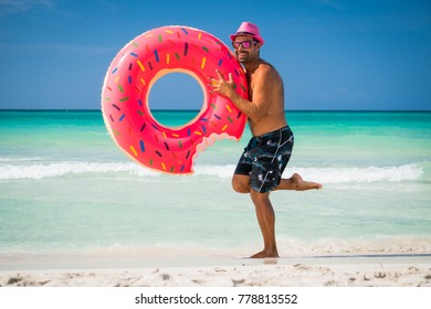 Happy handsome man in pink hat holds a big inflatable tube on the coast of Caribbean Sea in summer sunny day
