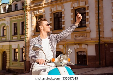 Happy handsome man sitting on the scooter making selfie photo