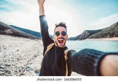 Happy handsome man takes a selfie portrait at vacation outdoor. Travel backpacker concept