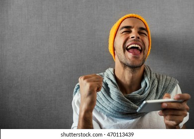 Happy handsome man with telephone. Win in a game. Wearing orange hat and gray scarf on gray background.