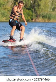 Happy handsome man wakesurfing in a lake and pulled by a boat.