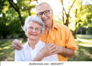 Happy and handsome senior couple hugging in park