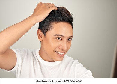 Happy handsome smiling Asian man touching his hair