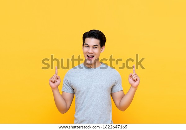 Happy handsome smiling young Asian man with hands poiting up to empty space above