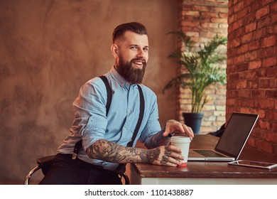 Happy handsome tattooed hipster in a shirt and suspenders holds takeaway coffee while sitting at the desk, working on a laptop in an office with a loft interior.