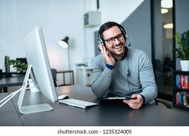 Happy handsome technical support agent talking to a client.
