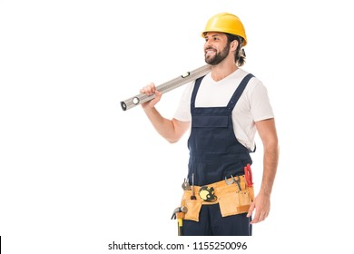 happy handsome workman holding level tool and looking away isolated on white