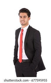 Happy handsome young businessman with hand in pocket smiling and standing confidently, guy wearing black suit and red tie, isolated on white background