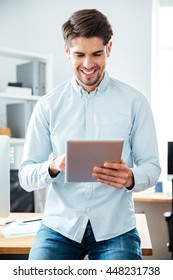 Happy handsome young businessman working and using tablet in office