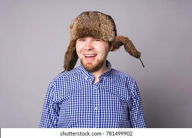 Happy handsome young man in cap with earflaps smiles in studio