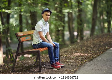 Happy handsome young man sitting on a bench in the park