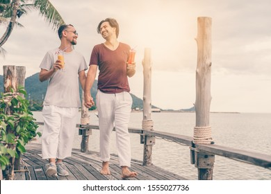 Happy handsome young men, gay family in a tropical resort with fruit necks, LGBT values, equal rights for everyone. Vacations and Travel.