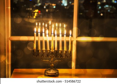 Happy Hanukkah. Low key image of jewish holiday Hanukkah with menorah by the window with the night view on Tel Aviv, Israel