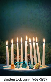 Happy Hanukkah Menorah with White Lighted Candles, Star of David Ornaments, Dreidles in dark still life with room or space for copy, text or your words.  Vertical card that is moody with cross filter