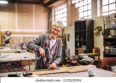 Happy hard working female working with electric drill in her workshop. Looking at camera.