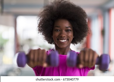 happy healthy african american woman working out in a gym on weight loss with dumbbells