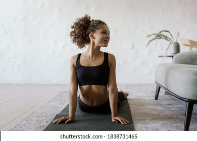 Happy and healthy afro american sporty and fit woman training at home on yoga mat, making sport exercise, stretch upper body, looking aside and smiling against copy space wall on background