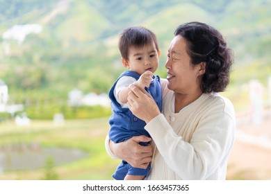 Happy and healthy asian grandmother is holding and playing with grandchild in the morning time on the background of nature, concept of multi generation living of asian family lifestyle.