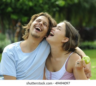 Happy healthy attractive couple with their apple in the park