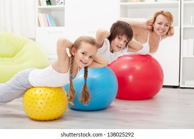Happy healthy family exercising at home with large gymnastic balls