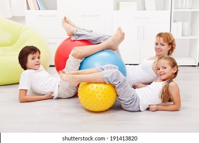 Happy healthy family with large gymnastic rubber balls laying on the floor at home