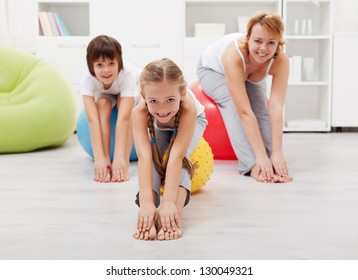 Happy healthy family - woman and kids - doing stretching exercises at home
