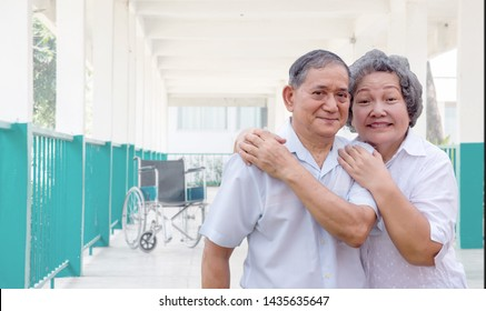 happy healthy grandmother and grandfather with empty wheelchair on walking way at hospital