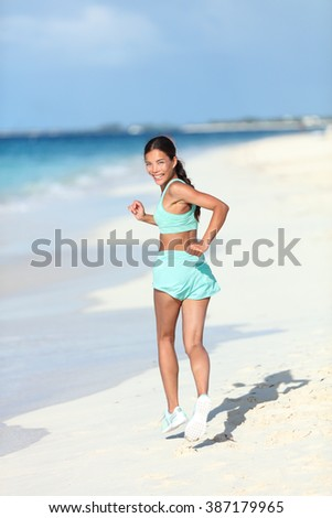 830b32498830 Happy healthy lifestyle woman runner jogging on white sand looking back  smiling at camera. Asian