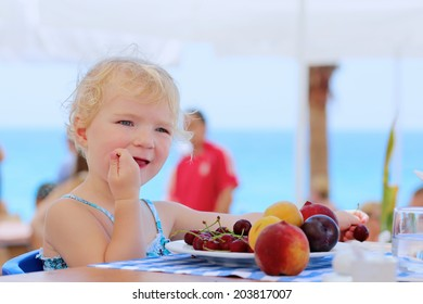 Happy healthy little child, cute blonde toddler girl, enjoying summer vacations eating sweet cherries and other fruits sitting in high chair at beach restaurant with sea view in tropical resort