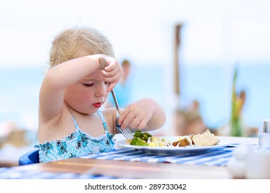 Happy healthy little child, cute blonde toddler girl, enjoying summer vacations eating potato, broccoli and other meal sitting in high chair at beach restaurant with sea view in tropical resort
