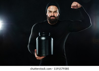 Happy and healthy muscular young fitness sports man with a jar of sports nutrition - protein, gainer and casein