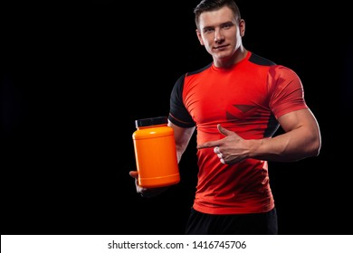 Happy and healthy muscular young fitness sports man with a jar of sports nutrition - protein, gainer and casein. Cheat meal