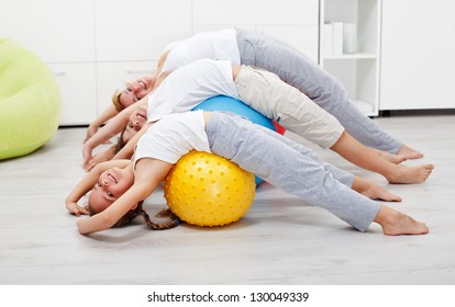 Happy healthy people exercising at home on large gymnastic balls