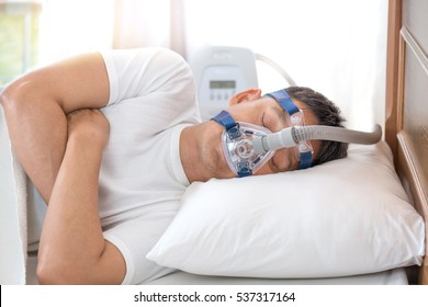 Happy and healthy senior man wearing Cpap mask sleeping smoothly all night long on his left side cross arms without snoring.Obstructive sleep apnea therapy.