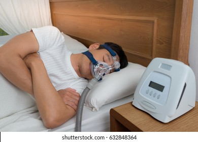 Happy and healthy senior man wearing Cpap mask sleeping smoothly all night long on his left side with cross arms without snoring, high angle view.Obstructive sleep apnea therapy.