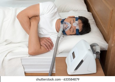 Happy and healthy senior man wearing Cpap mask sleeping smoothly all night long on his left side cross arms without snoring.Obstructive sleep apnea therapy, high angle view.