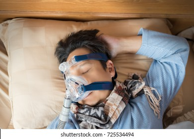 Happy and healthy senior man wearing cpap mask sleeping smoothly without snoring on his back open arm.Obstructive sleep apnea therapy,close up  top view.