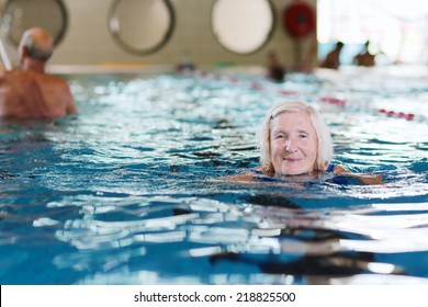 Happy healthy senior woman enjoying active lifestyle swimming in the pool