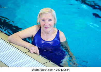 Happy healthy senior woman enjoying sportive lifestyle swimming in the pool - active retirement concept