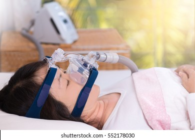 Happy and healthy senior woman wearing cpap mask sleeping smoothly without snoring on her back with blurred CPAP machine in background.Obstructive sleep apnea therapy,close up  side view.